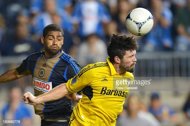 Danny O'Rourke of the Columbus Crew heads the ball away from Gabriel Gomez of the Philadelphia Union at PPL Park on August 29 2012 in Chester...