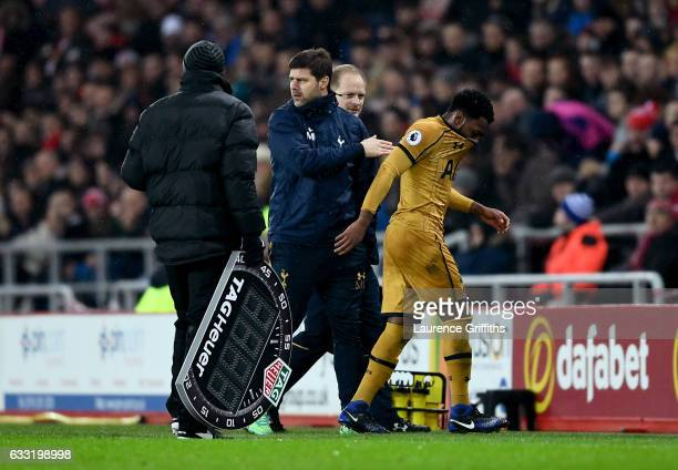 Danny Rose of Tottenham Hotspur is consoled by Mauricio Pochettino Manager of Tottenham Hotspur as he leaves the field injured during the Premier...