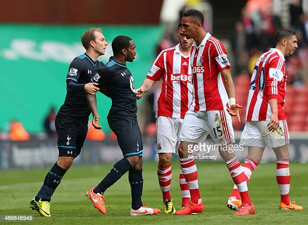 Danny Rose of Tottenham Hotspur is held back by Christian Eriksen after clashing with Geoff Cameron and Steven Nzonzi of Stoke City during the...