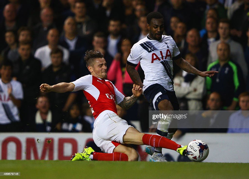 Danny Rose of Tottenham Hotspur is tackled by Mathieu Debuchy of Arsenal during the Capital One Cup third round match between Tottenham Hotspur and...