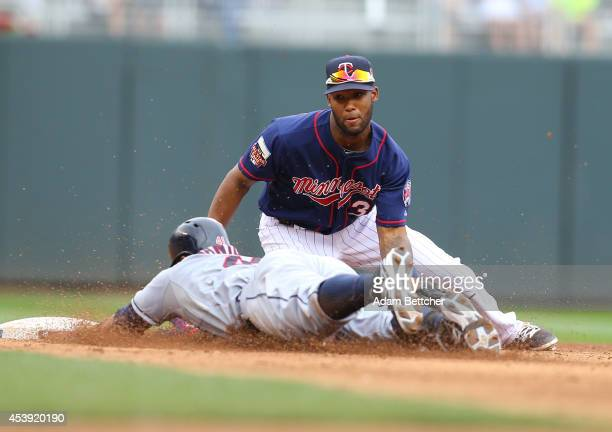 Danny Santana of the Minnesota Twins attempts the tag of Carlos Santana of the Cleveland Indians at Target Field on August 21 2014 in Minneapolis...