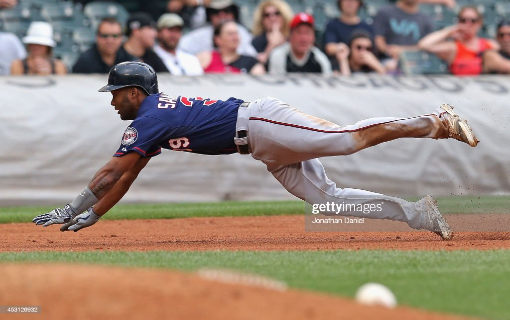 Danny Santana #39 of the Minnesota Twins dives into third base for a run-scoring triple in the 8th inning against the Chicago White Sox at U.S. Cellular Field on August 3, 2014 in Chicago, Illinois.