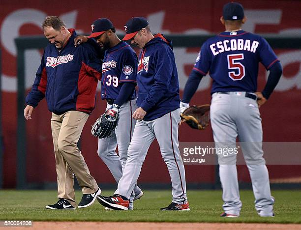 Danny Santana of the Minnesota Twins is helped off the field by a team trainer and manager Paul Molitor after injuring himself on a play in the sixth...