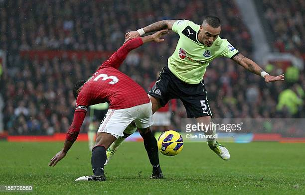 Danny Simpson of Newcastle United is tackled by Patrice Evra of Manchester United during the Barclays Premier League match between Manchester United...