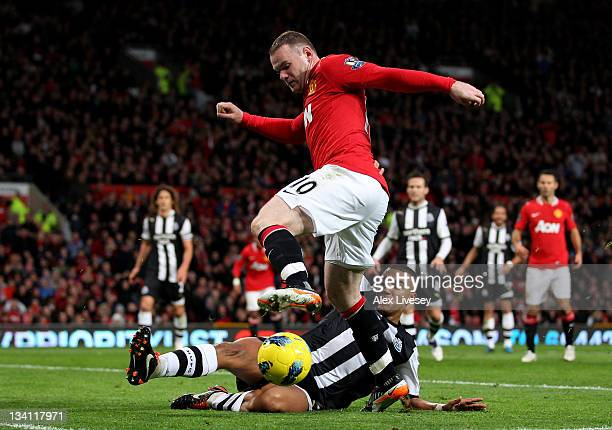 Danny Simpson of Newcastle United slides in to tackle Wayne Rooney of Manchester United during the Barclays Premier League match between Manchester...