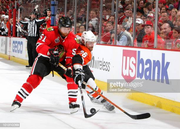 Danny Syvret of the Philadelphia Flyers and Brian Campbell of the Chicago Blackhawks battle for the puck during the third period of Game Two of the...