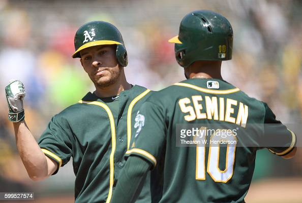 Danny Valencia and Marcus Semien of the Oakland Athletics celebrate after Valencia hit a tworun homer against the Los Angeles Angels of Anaheim in...