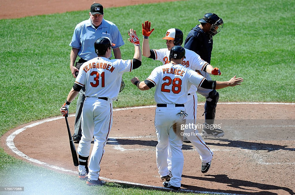 <a gi-track='captionPersonalityLinkClicked' href=/galleries/search?phrase=Danny+Valencia&family=editorial&specificpeople=5443820 ng-click='$event.stopPropagation()'>Danny Valencia</a> #35 of the Baltimore Orioles celebrates with <a gi-track='captionPersonalityLinkClicked' href=/galleries/search?phrase=Taylor+Teagarden&family=editorial&specificpeople=835625 ng-click='$event.stopPropagation()'>Taylor Teagarden</a> and Steve Pearce #28 after hitting a home run in the sixth inning against the Seattle Mariners at Oriole Park at Camden Yards on August 4, 2013 in Baltimore, Maryland.