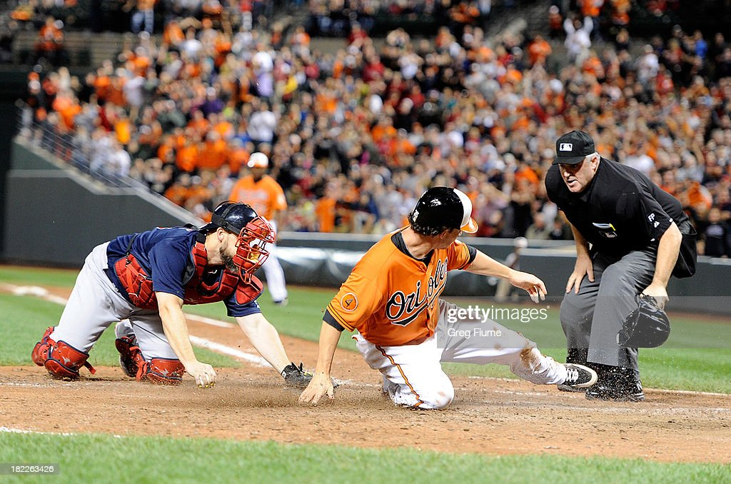<a gi-track='captionPersonalityLinkClicked' href=/galleries/search?phrase=Danny+Valencia&family=editorial&specificpeople=5443820 ng-click='$event.stopPropagation()'>Danny Valencia</a> #35 of the Baltimore Orioles scores the winning run in the eighth inning ahead of the tag of <a gi-track='captionPersonalityLinkClicked' href=/galleries/search?phrase=David+Ross&family=editorial&specificpeople=210843 ng-click='$event.stopPropagation()'>David Ross</a> #3 of the Boston Red Sox at Oriole Park at Camden Yards on September 28, 2013 in Baltimore, Maryland. Baltimore won the game 6-5.