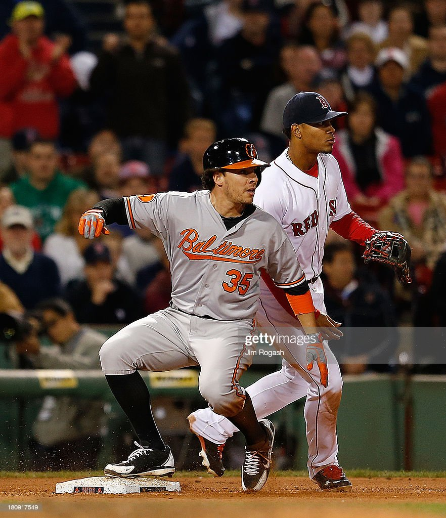 Danny Valencia #35 of the Baltimore Orioles slides in to third on a triple as Xander Bogaerts #72 of the Boston Red Sox defends the bag in the 9th inning at Fenway Park on September 17 in Boston, Massachusetts.