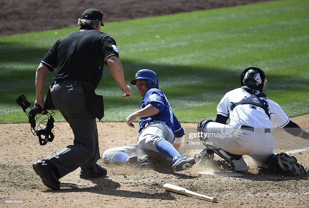 Danny Valencia #19 of the Kansas City Royals scores ahead of the throw to Rene Rivera #44 of the San Diego Padres during the ninth inning of a baseball game at Petco Park May 7, 2014 in San Diego, California.