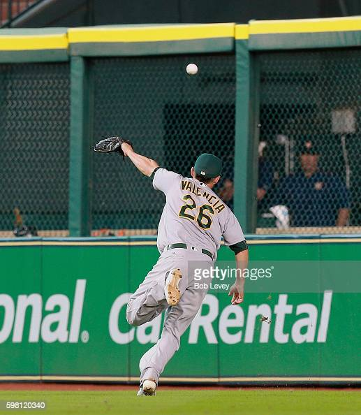 Danny Valencia of the Oakland Athletics can't track down a line drive by Jose Altuve of the Houston Astros in the eighth inning at Minute Maid Park...