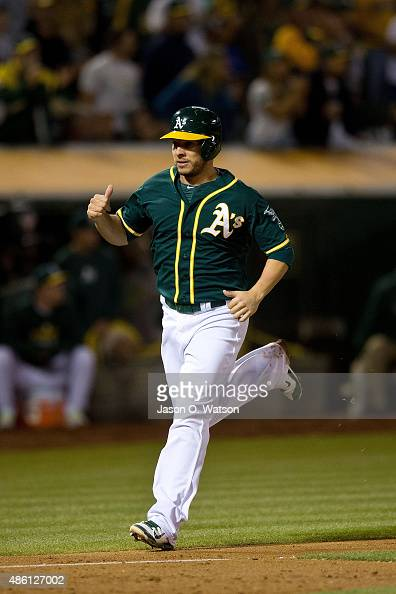 Danny Valencia of the Oakland Athletics celebrates after scoring a run against the Los Angeles Angels of Anaheim during the third inning at Oco...