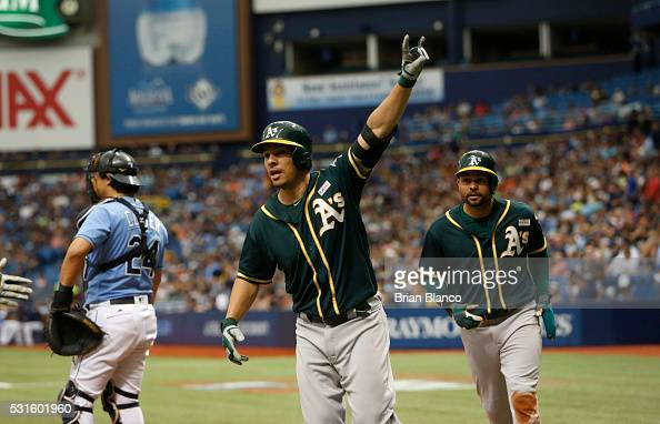 Danny Valencia of the Oakland Athletics center and teammate Coco Crisp run around catcher Hank Conger of the Tampa Bay Rays after both scoring off of...