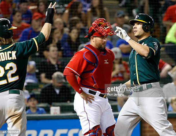 Danny Valencia of the Oakland Athletics crosses home plate and celebrates with teammate Josh Reddick after hitting a tworun home run as catcher Bobby...