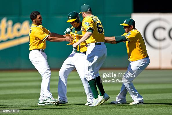 Danny Valencia of the Oakland Athletics is congratulated by Marcus Semien and Sean Doolittle after hitting a walk off RBI single after the game...