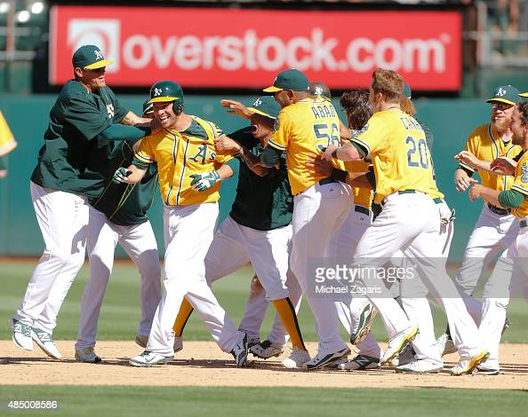 Danny Valencia of the Oakland Athletics is mobbed by teammates after hitting a walkoff single following the game against the Houston Astros at Oco...