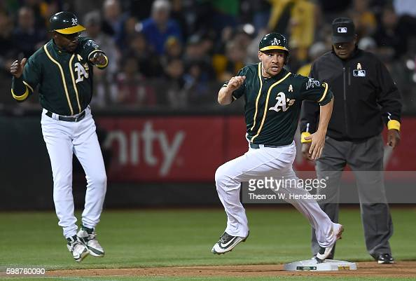 Danny Valencia of the Oakland Athletics rounds third to score waved home by third base coach Ron Washington against the Boston Red Sox in the bottom...