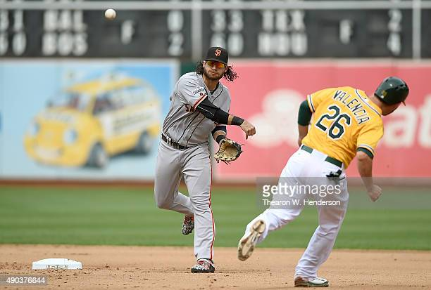 Danny Valencia of the Oakland Athletics runs out of the way of Brandon Crawford of the San Francisco Giants who gets his throw off to complete the...