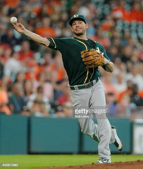 Danny Valencia of the Oakland Athletics throws to first base as Jose Altuve of the Houston Astros lays down a bunt in the third inning at Minute Maid...