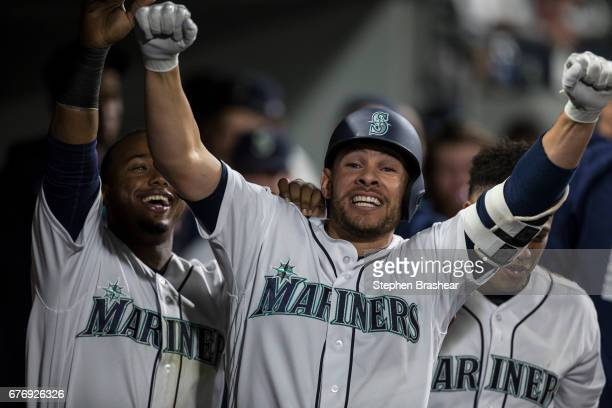 Danny Valencia of the Seattle Mariners celebrates with teammates Jean Segura and Robinson Cano hitting a solo home run off of starting pitcher Matt...