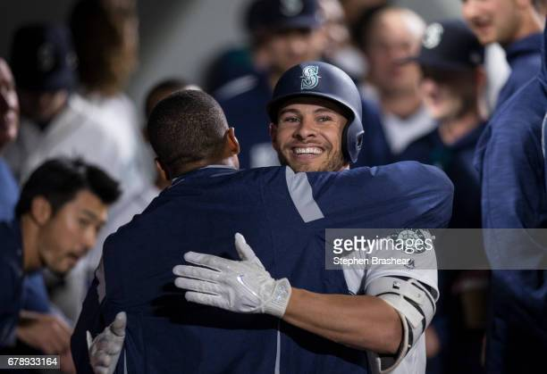 Danny Valencia of the Seattle Mariners gets a hug from starting pitcher Ariel Miranda of the Seattle Mariners in the dugout after Valencia hit a solo...