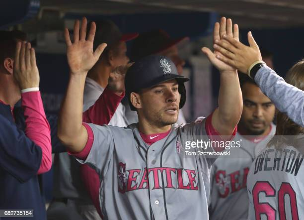 Danny Valencia of the Seattle Mariners is congratulated by teammates in the dugout after scoring a run on an RBI single by Jarrod Dyson in the sixth...