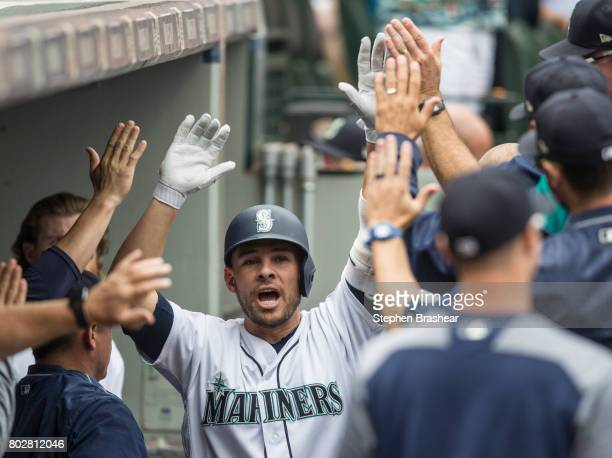 Danny Valencia of the Seattle Mariners is congratulated by teammates in the dugout after hitting a solo home run off starting pitcher Mark Leiter Jr...