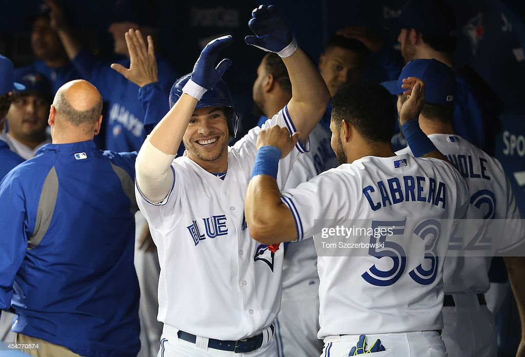 Danny Valencia #15 of the Toronto Blue Jays is congratulated by Melky Cabrera #53 after hitting a three-run home run in the seventh inning during MLB game action against the Boston Red Sox on August 27, 2014 at Rogers Centre in Toronto, Ontario, Canada.