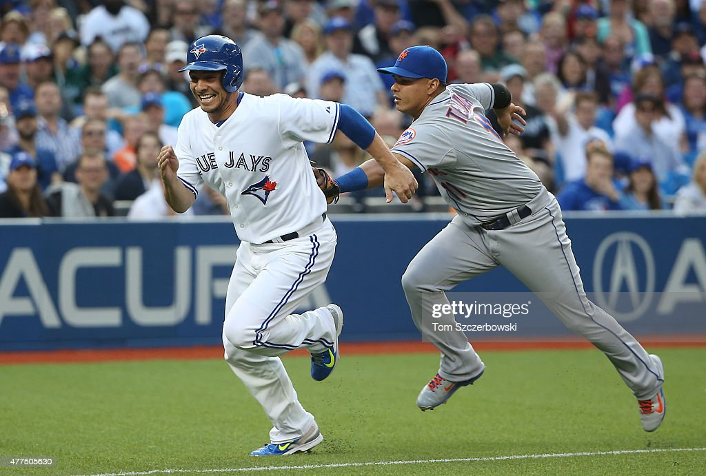 Danny Valencia #23 of the Toronto Blue Jays is tagged out by Ruben Tejada #11 of the New York Mets as he is caught in a run-down between home plate and third base in the second inning during MLB game action on June 17, 2015 at Rogers Centre in Toronto, Ontario, Canada.