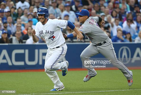 Danny Valencia of the Toronto Blue Jays is tagged out by Ruben Tejada of the New York Mets as he is caught in a rundown between home plate and third...