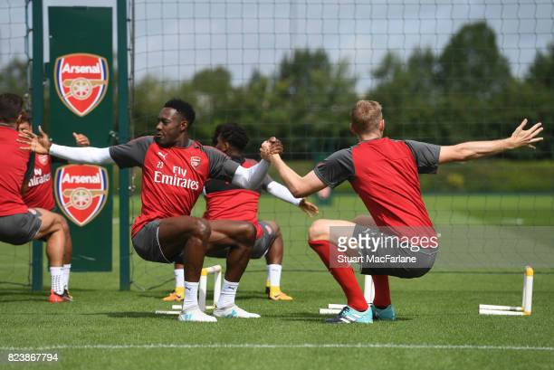 Danny Welbeck and Per Mertesacker of Arsenal stretch during a training session at London Colney on July 28 2017 in St Albans England