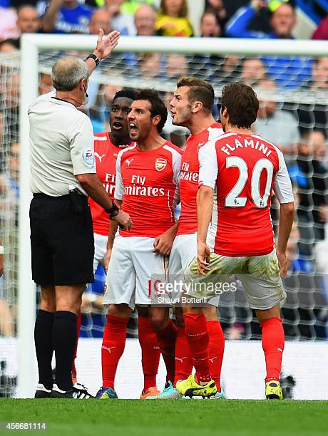 Danny Welbeck Jack Wilshere Santi Cazorla and Mathieu Flamini of Arsenal surround Referee Martin Atkinson during the Barclays Premier League match...