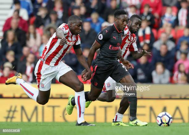 Danny Welbeck of Arsenal attempts to get past Kurt Zouma of Stoke City and Mame Biram Diouf of Stoke City during the Premier League match between...