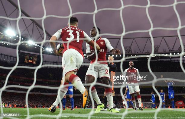 Danny Welbeck of Arsenal celebrates with teammate Sead Kolasinac after scoring his team's second goal during the Premier League match between Arsenal...