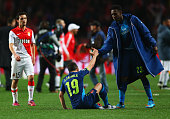 Danny Welbeck of Arsenal consoles team mate Santi Cazorla as they eliminated after the UEFA Champions League round of 16 second leg match between AS...