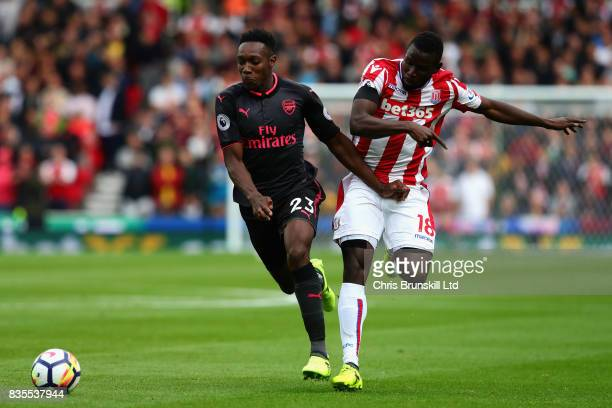 Danny Welbeck of Arsenal dribbles past Mame Biram Diouf of Stoke City during the Premier League match between Stoke City and Arsenal at Bet365...