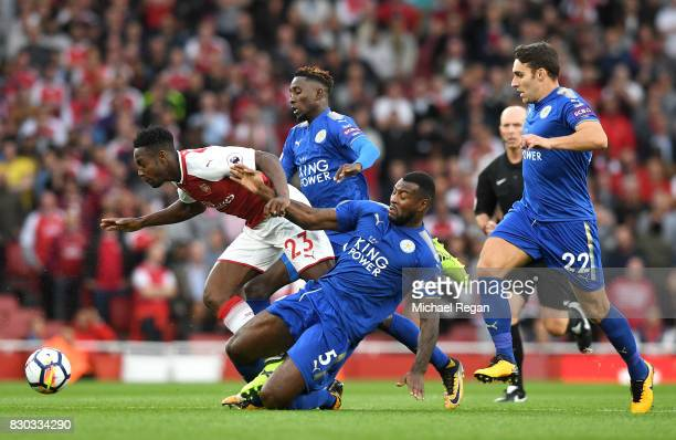 Danny Welbeck of Arsenal is tackled by Wes Morgan of Leicester City during the Premier League match between Arsenal and Leicester City at the...