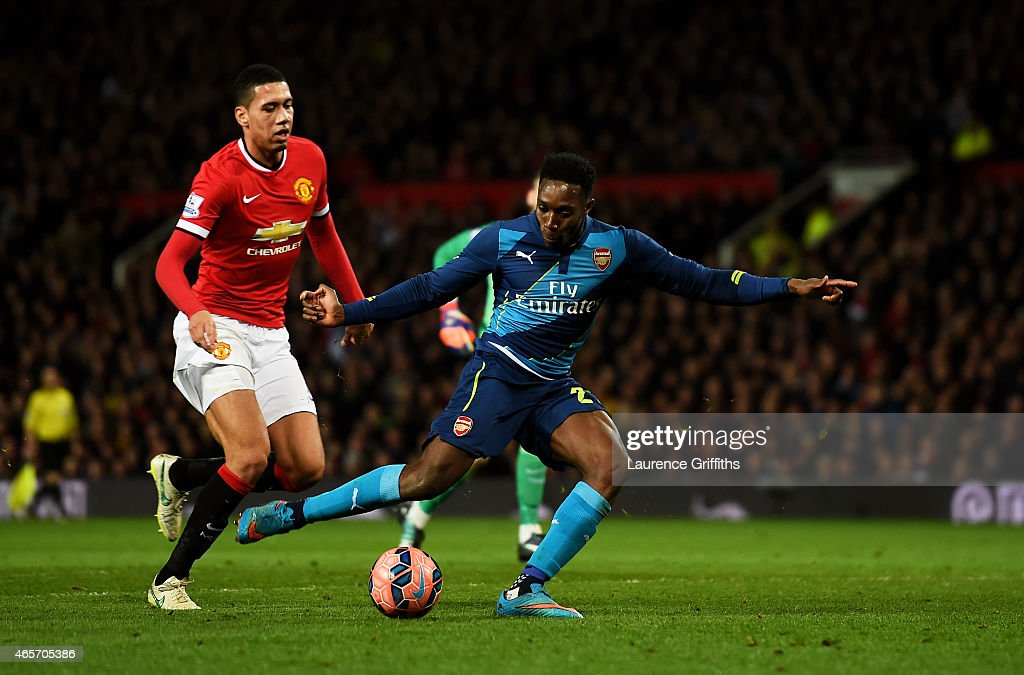 Danny Welbeck of Arsenal scores his team's second goal despite the attentions from Chris Smalling of Manchester United during the FA Cup Quarter Final match between Manchester United and Arsenal at Old Trafford on March 9, 2015 in Manchester, England.