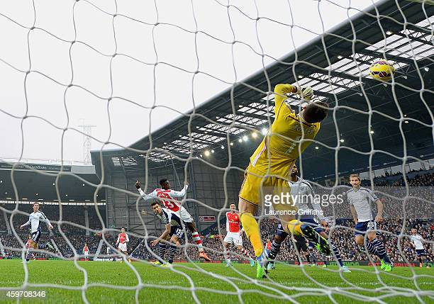 Danny Welbeck of Arsenal scores the first goal past Ben Foster of West Brom during the Barclays Premier League match between West Bromwich Albion and...