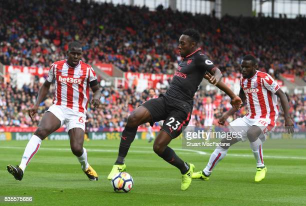 Danny Welbeck of Arsenal takes on Kurt Kouma and Mame Diouf of Stoke during the Premier League match between Stoke City and Arsenal at Bet365 Stadium...