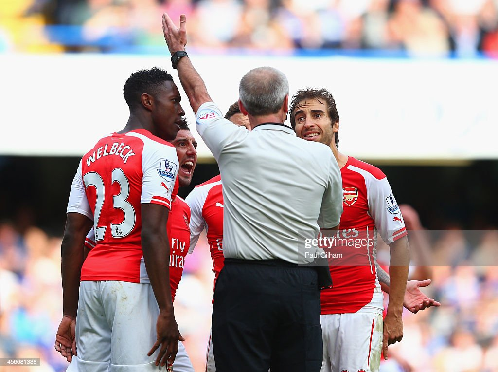 Danny Welbeck Santi Cazorla and Mathieu Flamini of Arsenal surround Referee Martin Atkinson during the Barclays Premier League match between Chelsea...