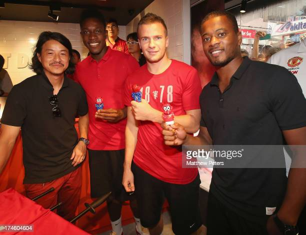 Danny Welbeck Tom Cleverley and Patrice Evra of Manchester United FC pose with local sculptor Michael Lau and table football figures of themselves...