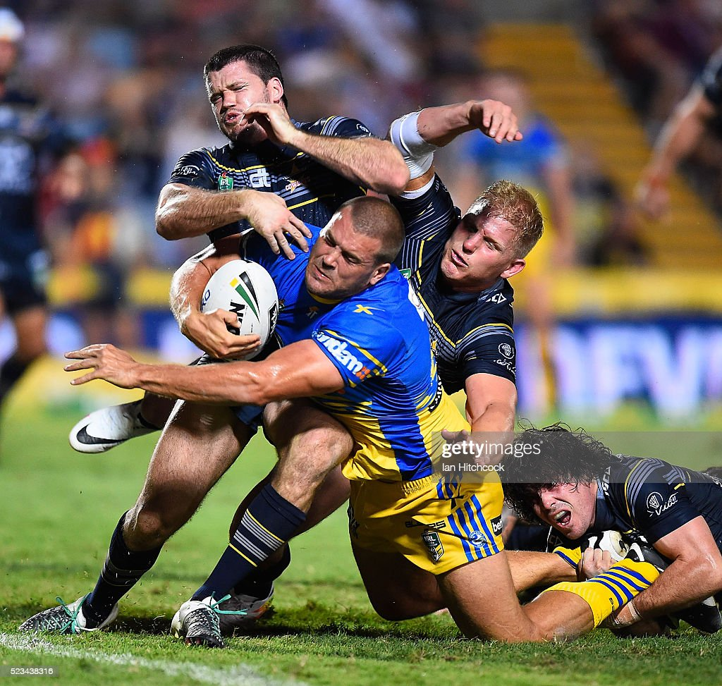 Danny Wicks of the Eels is tackled by Lachlan Coote, Ben Hannant and Jake Granville of the Cowboys during the round eight NRL match between the North Queensland Cowboys and the Parramatta Eels at 1300SMILES Stadium on April 23, 2016 in Townsville, Australia.