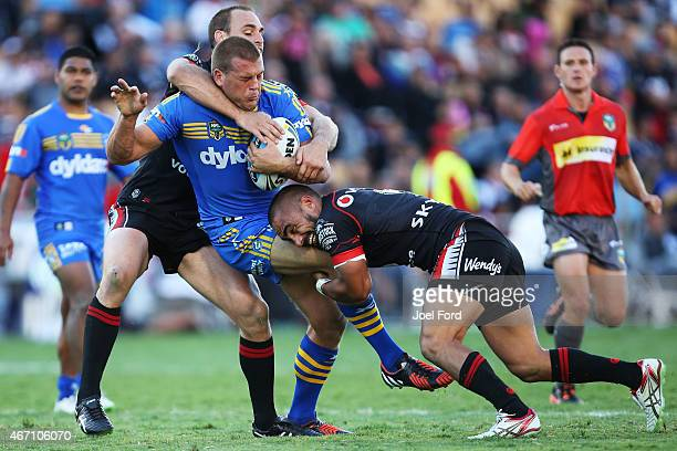 Danny Wicks of the Parramatta Eels is tackled by Simon Mannering and Thomas Leuluai of the New Zealand Warriors during the round three NRL match...