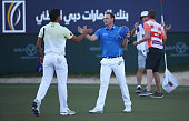 Danny Willett of England celebrates his victory on the 18th green as he shakes hands with Rafa CabreraBello of Spain during the final round of the...