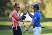 Danny Willett of England celebrates his victory with caddie Jonathan Smart on the 18th green during the final round of the Omega Dubai Desert Classic...