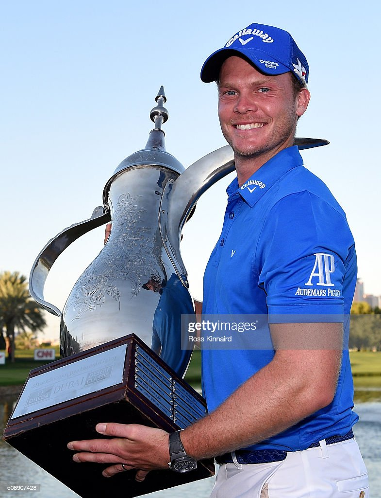 Danny Willett of England celebrates with the winners trophy after the final round of the Omega Dubai Desert Classic on the Majlis Course at the...