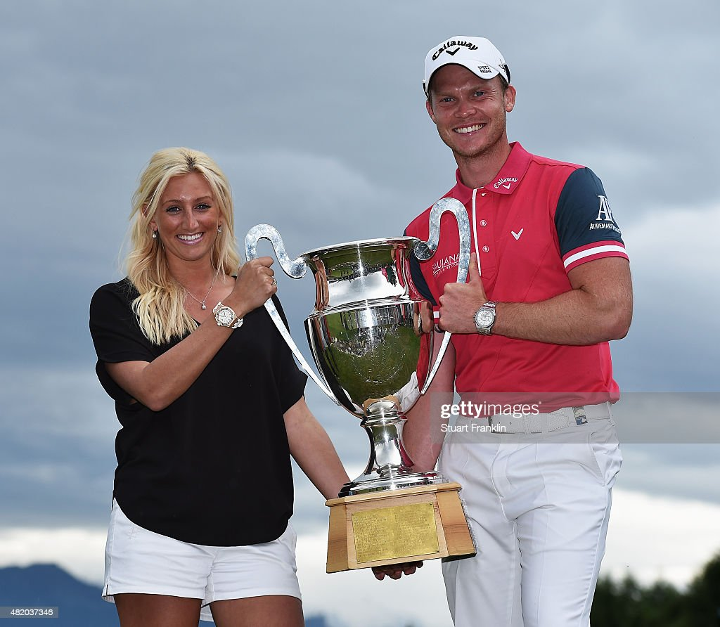 Danny Willett of England holds the trophy with his wife Nicole Willett after winning the Omega European Masters at CranssurSierre Golf Club on July...