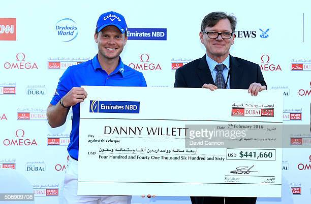 Danny Willett of England is presented with his winners cheque after the final round of the 2016 Omega Dubai Desert Classic on the Majlis Course at...